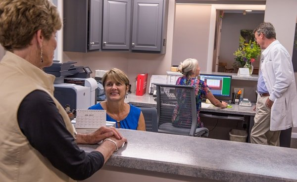 A patient talking to the front office staff at Lyme Road Dental