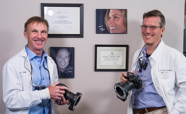 Dr. Melkers and Dr. Wonsavage smiling and holding digital cameras