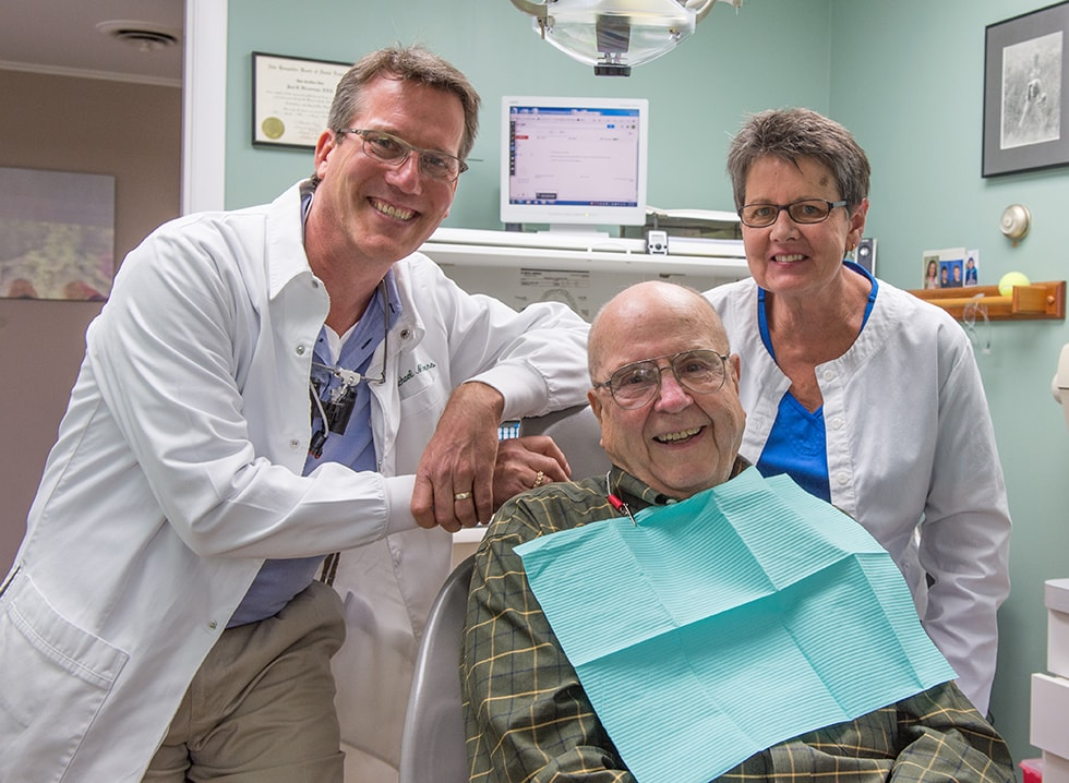 Mobile and tablet image of Dr. Michael Melkers with a happy patient