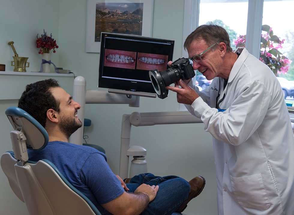 Mobile and tablet image of Dr. Paul Wonsavage taking a photo of a patient's smile