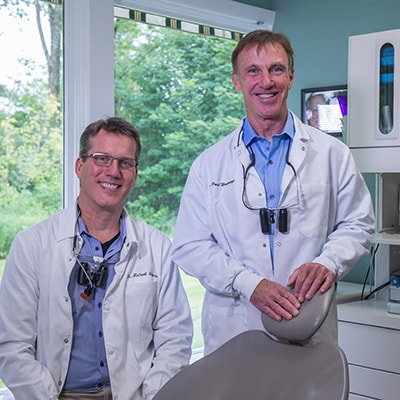 Dr. Michael Melkers and Dr. Wonsavage standing in a treatment room in their lab coats. Our dentists are specially trained with dental implants in Hanover, NH