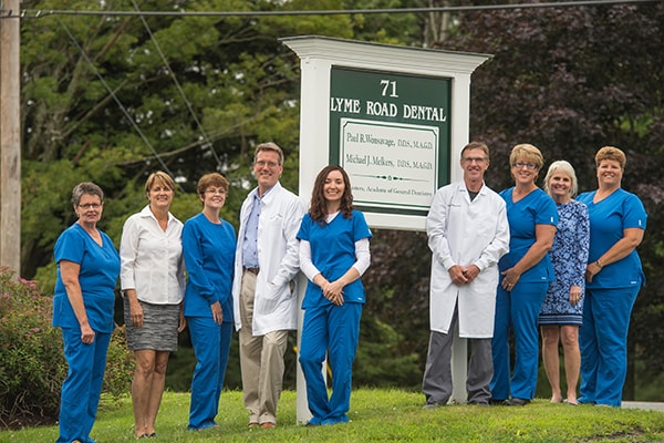 The Lyme Road Dental team standing outside right by their office sign