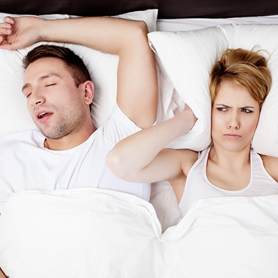 Wife lacking sleep cause of snoring husband and sleep apnea to show that we offer sleep apnea treatment as part of our family dentistry in Hanover, NH