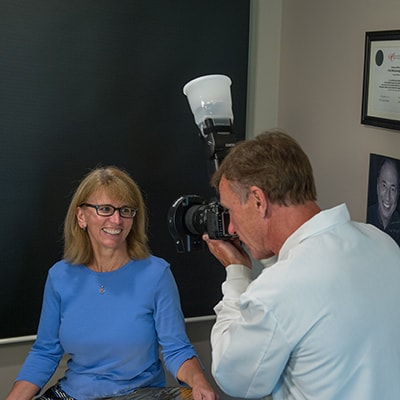 Dr. Paul Wonsavage taking a photo of a patient after smile design