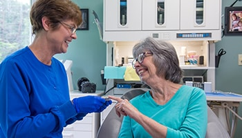 A team member from Lyme Road Dental laughing with a patient