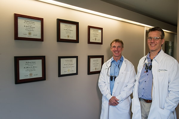 Each Hanover NH Dentist standing next to their accomplishments of providing extraordinary dentistry