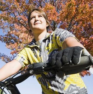 Girl bicycling admiring autumn leaves.