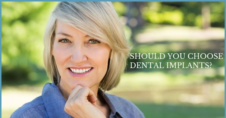 Should you choose dental implants? An attractive mature woman with her hand on her chin ponders if she is a good dental implants candidate.
